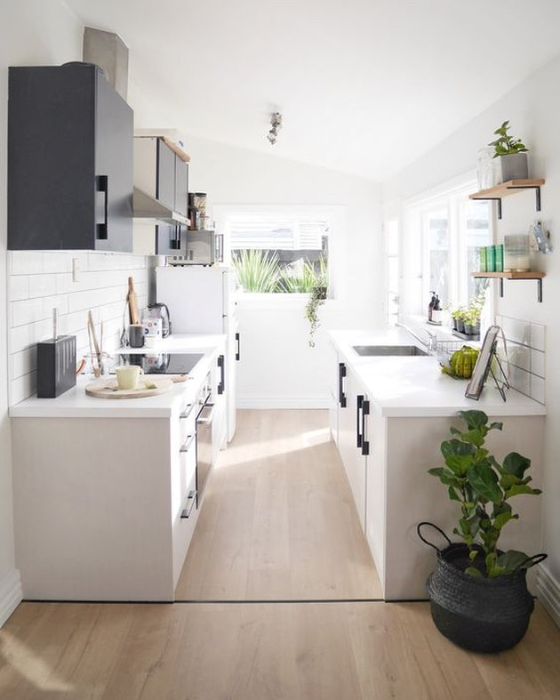 white galley kitchen with subway tile clad walls