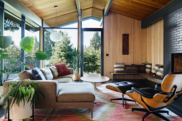 midcentury modern living room with Eames lounge chair and ottoman and black tile fireplace surround