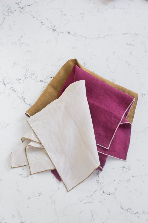 tan, beige, and maroon napkins on marble table