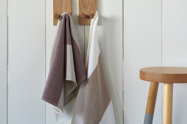 neutral kitchen towels hanging on pegs