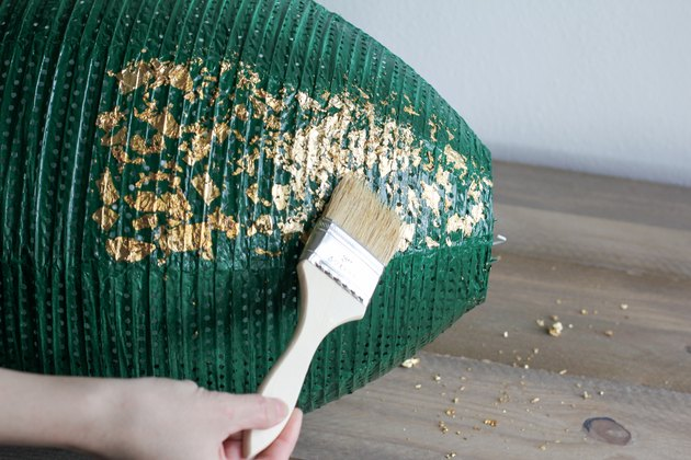 Brushing off excess gold leaf flakes