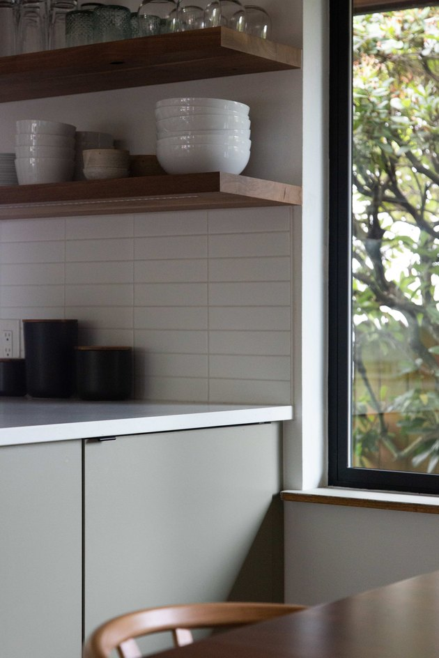 Open shelving and white subway backsplash in kitchen.