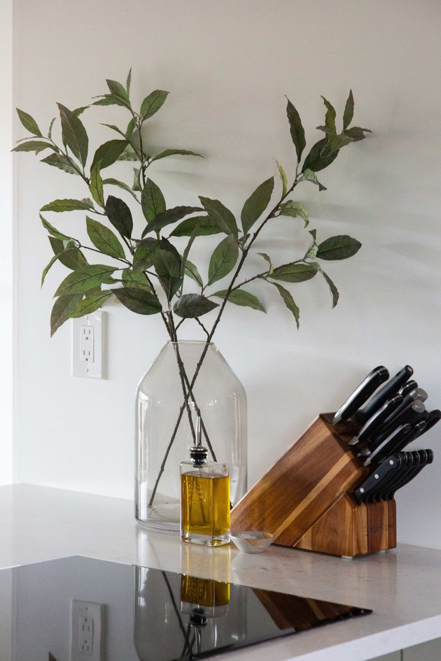 GE cooktop with set of knives and plant in glass vase