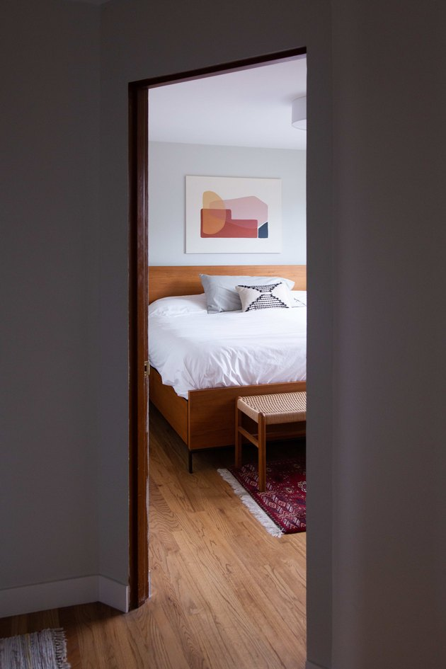 A peek into the master bedroom with wood bed frame and art over bed