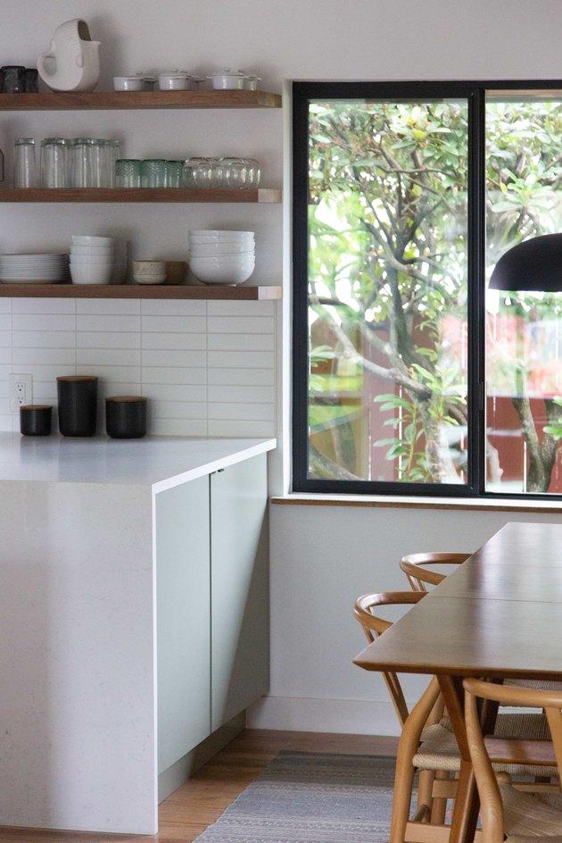Kitchen windows bringing in natural light to minimal kitchen