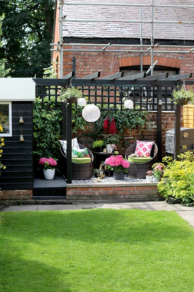 Colorful small patio ideas with paper lanterns, bright throw pillows, and flowers