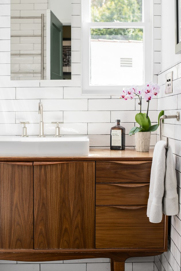 wood dresser bathroom vanity, white ceramic vessel sink, silver faucet and handles, white subway tile wall, window, white towel hung up, vase of orchids