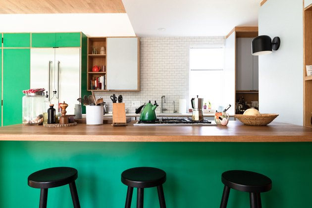 Kitchen counter, green paint, black counter stools, wood countertop