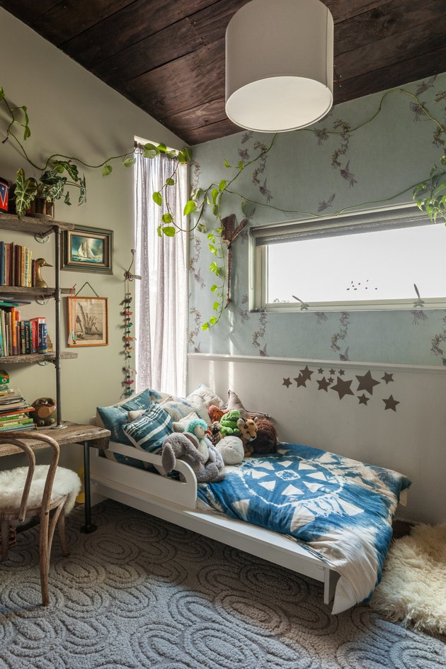 bohemian kids bedroom idea with botanical wallpaper and plants draped around windows