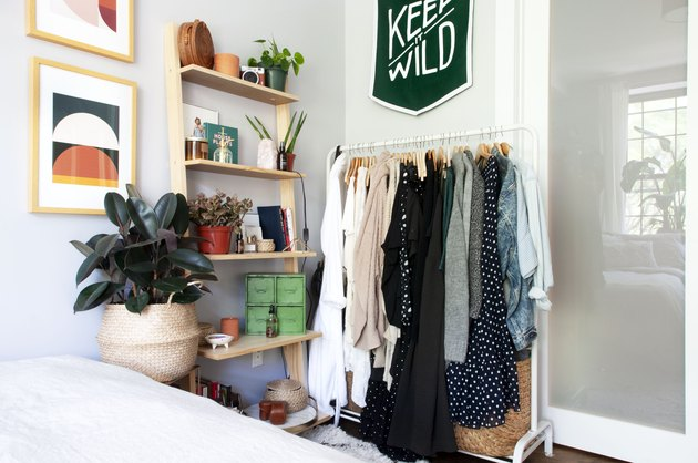 small bedroom idea with clothing rack near leaning shelving unit