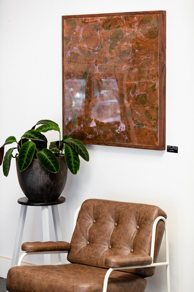Artwork on wall over leather chair and planter with green plant