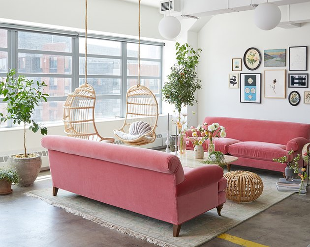 contemporary living room with velvet pink sofas and hanging chairs