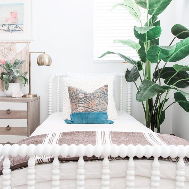 bohemian kids bedroom idea with potted plants and white bed