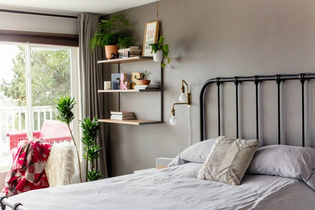 small bedroom idea with shelving on wall near bed and window