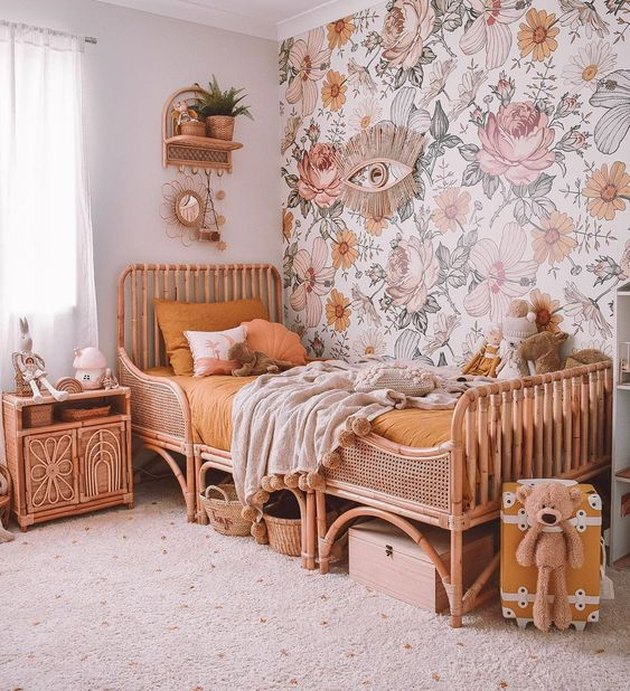rattan bed and nightstand in bohemian kids bedroom idea with floral wallpaper