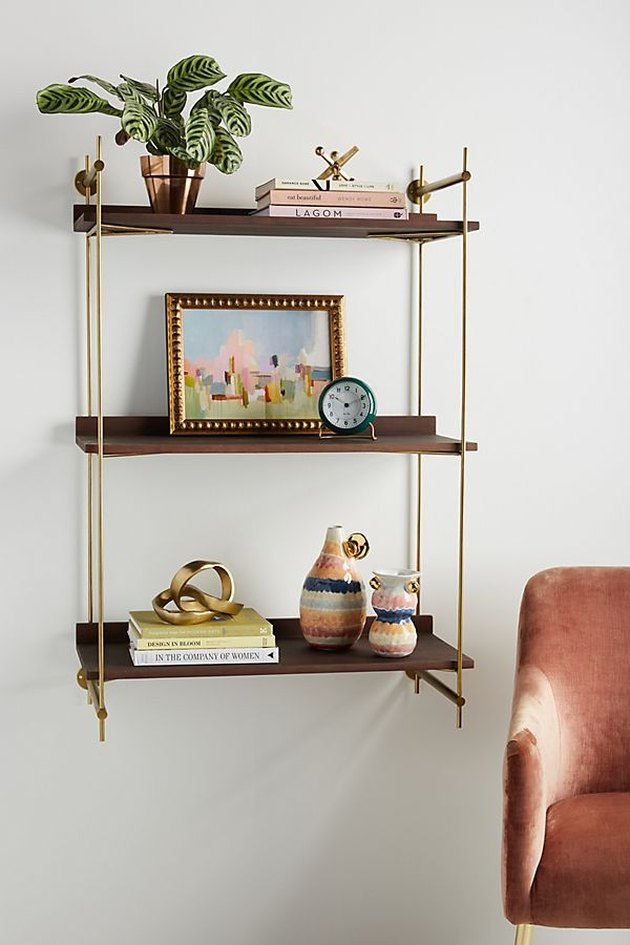 Small wall-mounted shelving unit with three dark wooden shelves and brass accents