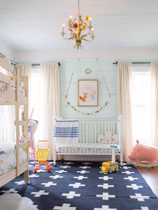 blue nursery idea with aqua shiplap walls and dark area rug