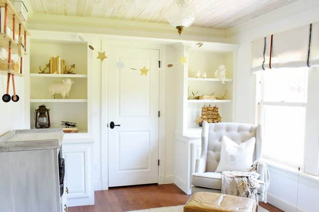 French farmhouse nursery idea with built-in shelving and tufted wingback rocking chair