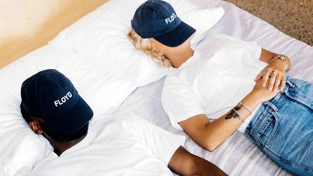 people in bed wearing baseball cap