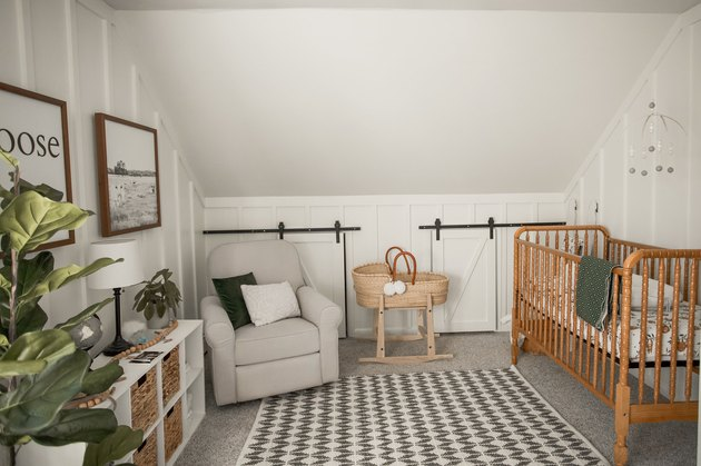 Vintage-inspired nursery idea with wooden crib and small barn-style doors