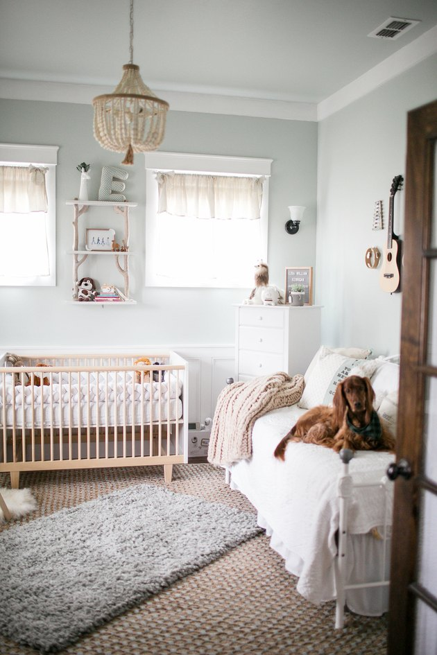 Blue nursery idea with light woods and layered rugs