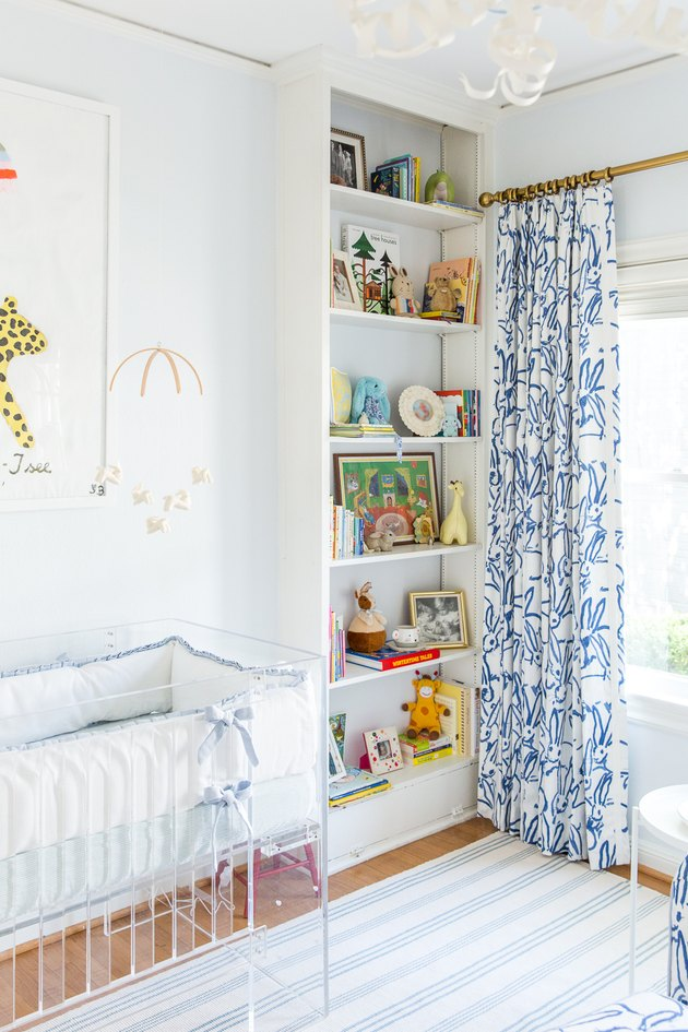 Blue nursery idea with patterned drapery at window and built-in bookcase filled with books and toys