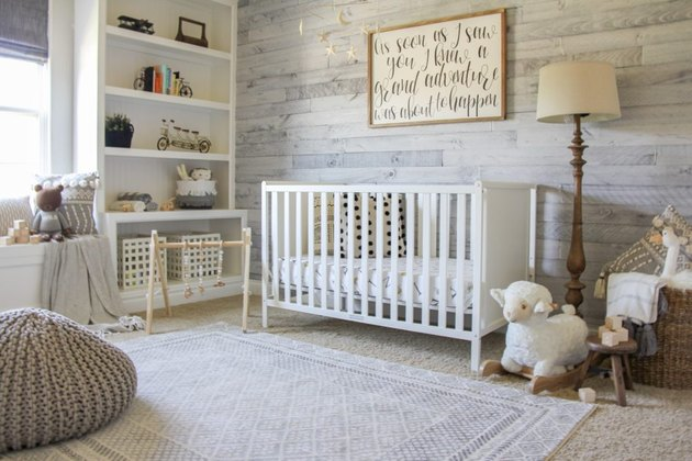 farmhouse nursery idea with wood paneled wall and open shelving