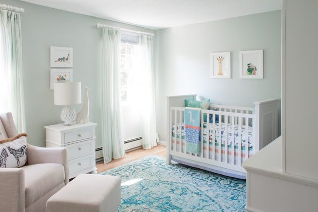 Blue nursery idea with white furniture and blue area rug