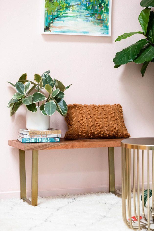 Bench with textured pillow and plant on design books