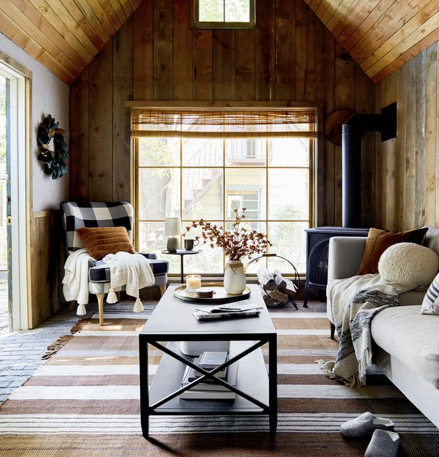 cozy living rooom with wood paneled walls and a buffalo check wingback chair