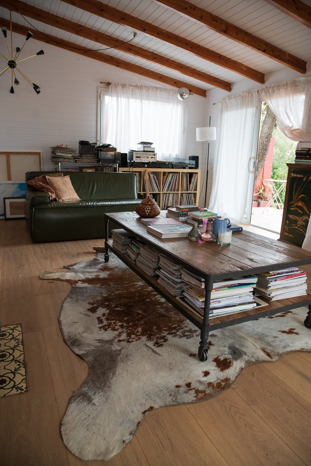 Sloped ceiling with beams, animal skin rug, and coffee table