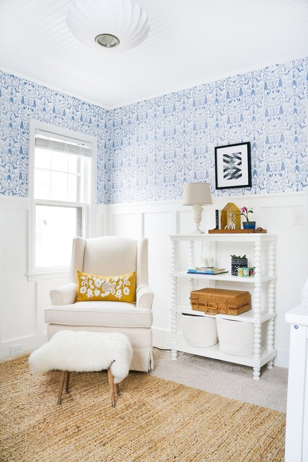 Blue nursery idea with patterned wallpaper and white wall paneling