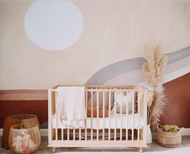 nursery idea for 2020 with warm earth tones and artistic mural on wall