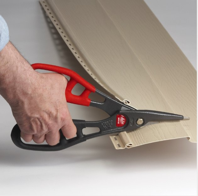 Cutting vinyl siding with tin snips.