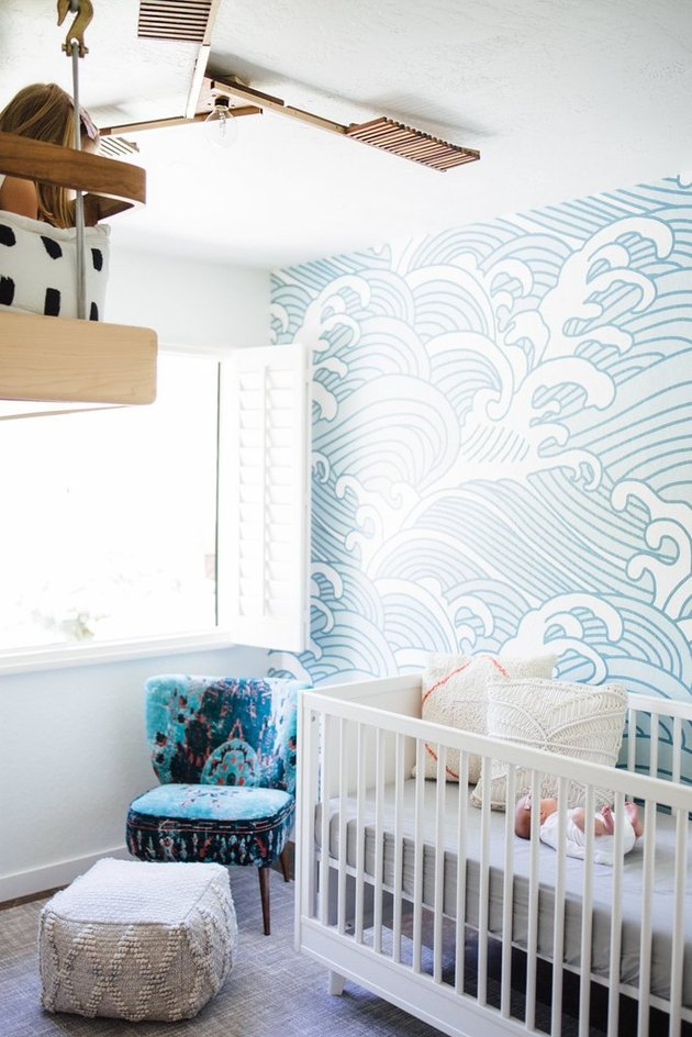 blue nursery idea with mural wallpaper and white crib near window with shutters