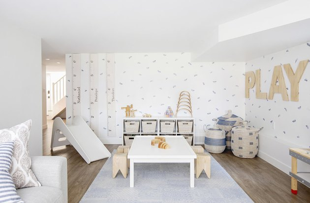 kids playroom idea with slide and table and stools for arts and crafts and sofa
