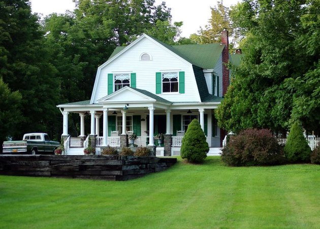 A barn home with green shutters and columns