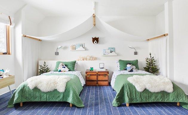Зеленая детская спальня с балдахином над двумя раздельными кроватями с зеленым постельным бельем
