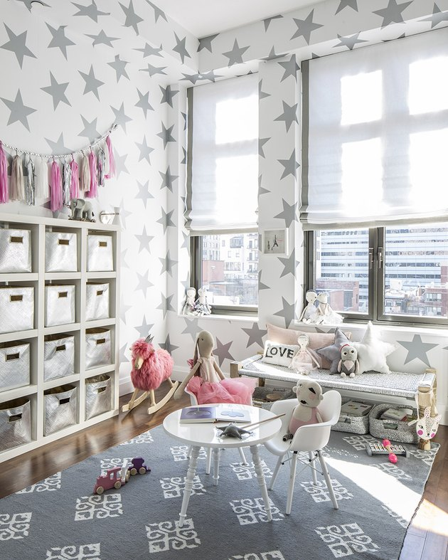 kids playroom idea with star wallpaper and white furniture with hot pink toys