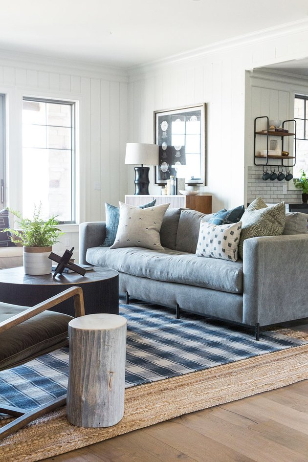 traditinal living room with plaid rug layered over a jute rug