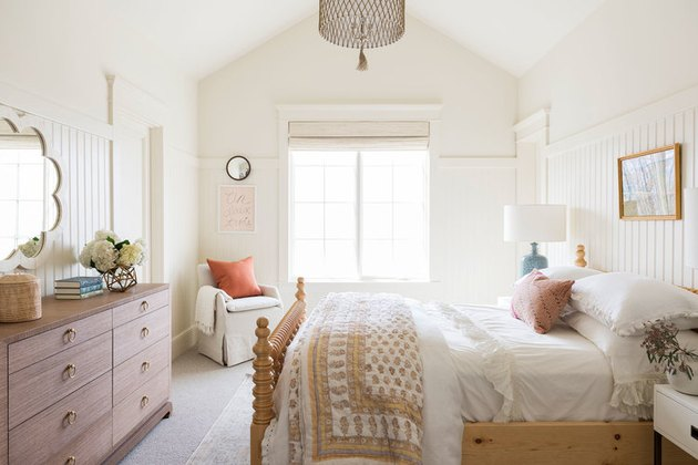 White and airy kids' bedroom idea with wall paneling and mirror above dresser