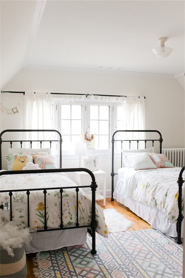 Black and white kids' bedroom idea with metal bed frames and drapery at window