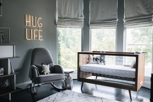 Gray baby nursery idea with crib in front of bay windows with Roman shades and neon sign hanging on wall above rocking chair