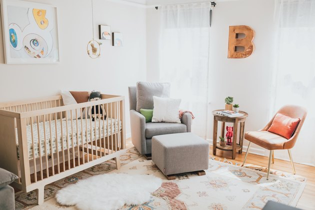 Modern baby nursery idea with wooden crib next to rocking chair by windows