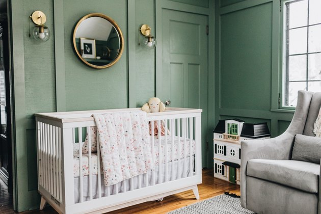 Green baby nursery idea with white crib and mirror hanging on wall with wall sconces