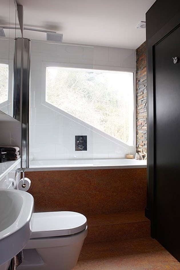 modern black bathroom with cork flooring and brick accent wall