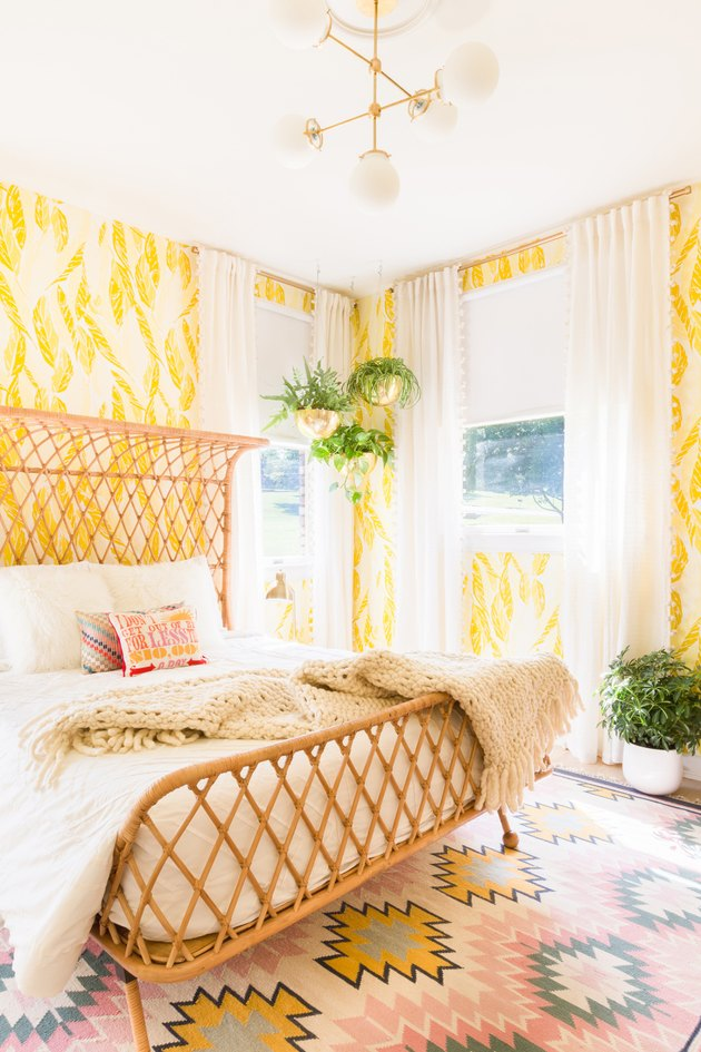bedroom with yellow wallpaper and woven rattan bed