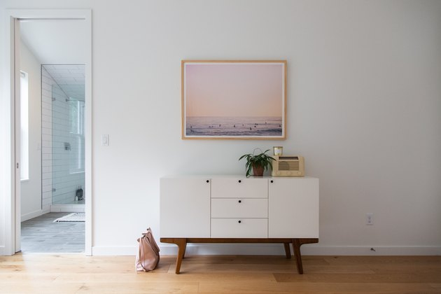 minimalistic white credenza with white wall and hardwood flooring