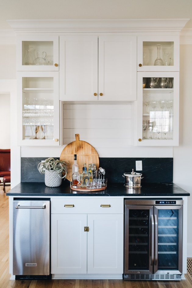 kitchen space with white glass cabinets and dark countertop