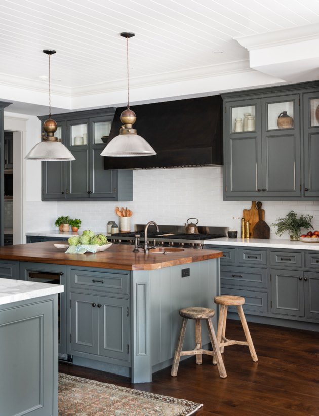 kitchen space with dark cabinets and two hanging lights